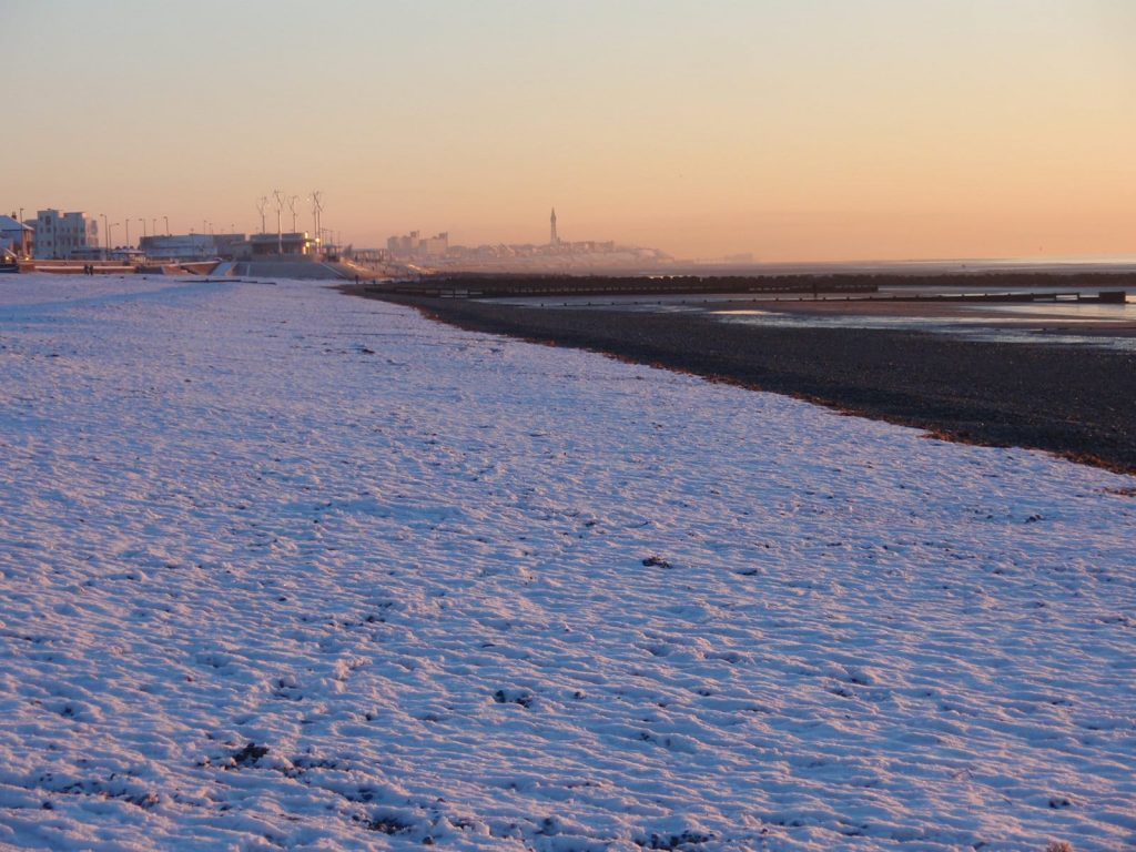 Snow at the seaside. Sunset over a snow covered beach