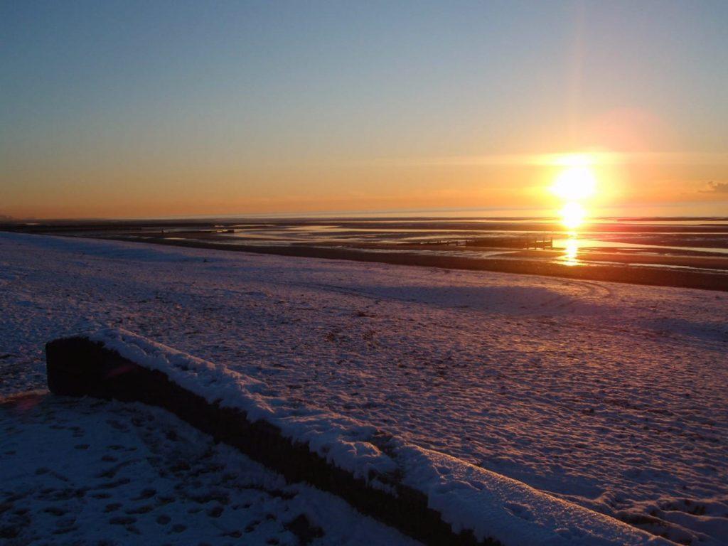 Sunset over snow at the seaside on a Fylde Coast Beach