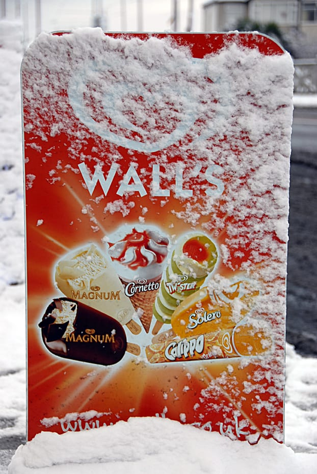 Ice cream sign, covered in ice during snow at the seaside