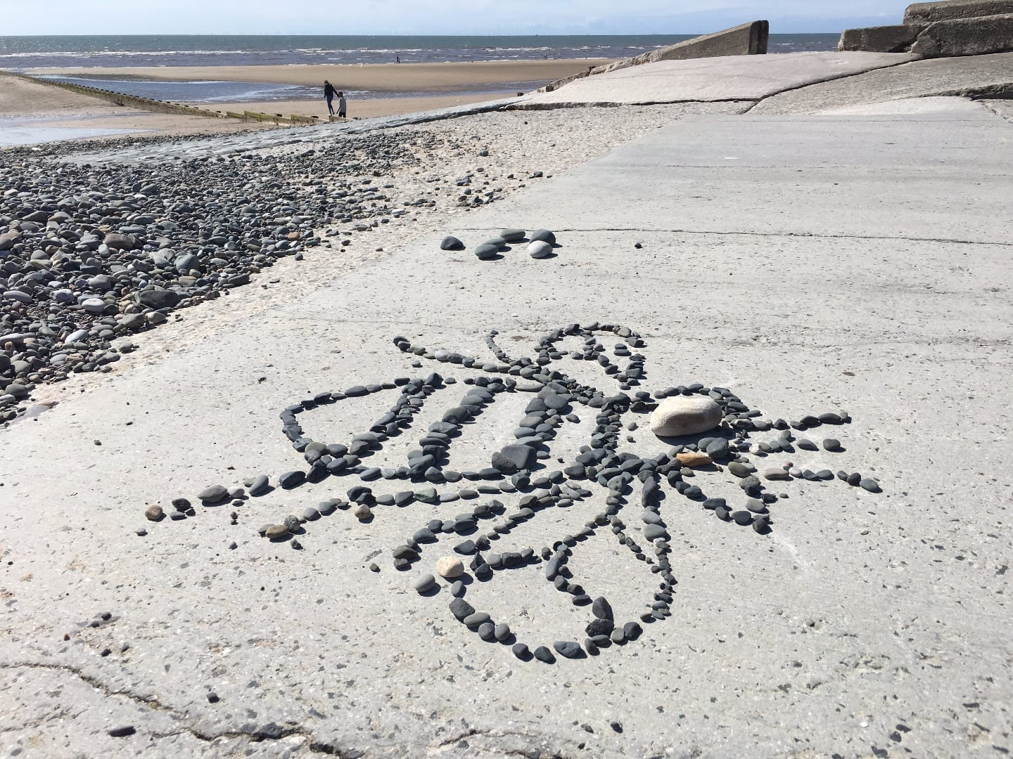 Manchester Bee made in pebbles on the sea wall at Rossall