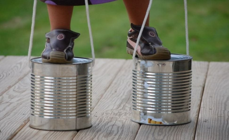 Tin can stilts, one of the games we played in the olden days